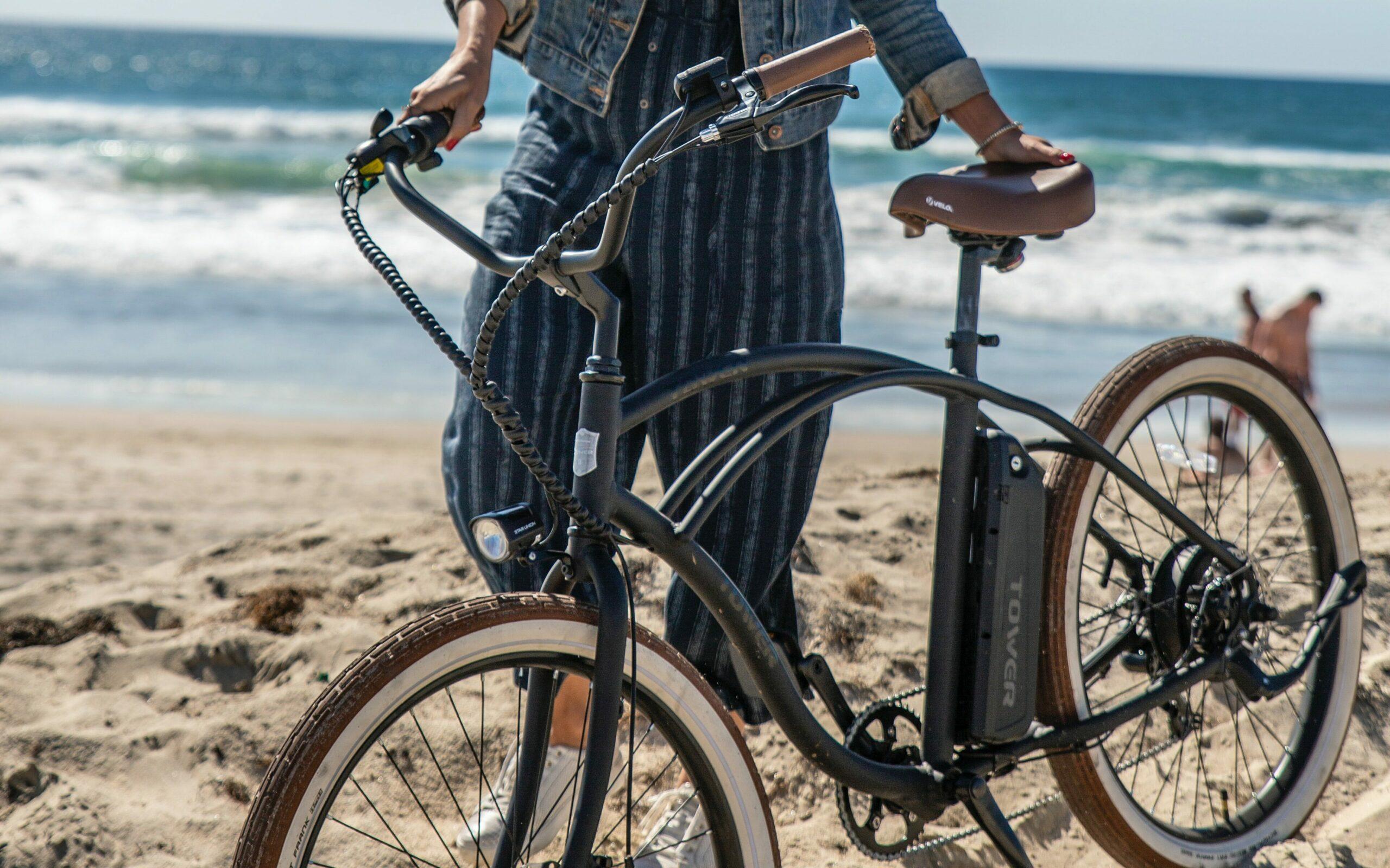 Jente med elsykkel på strand