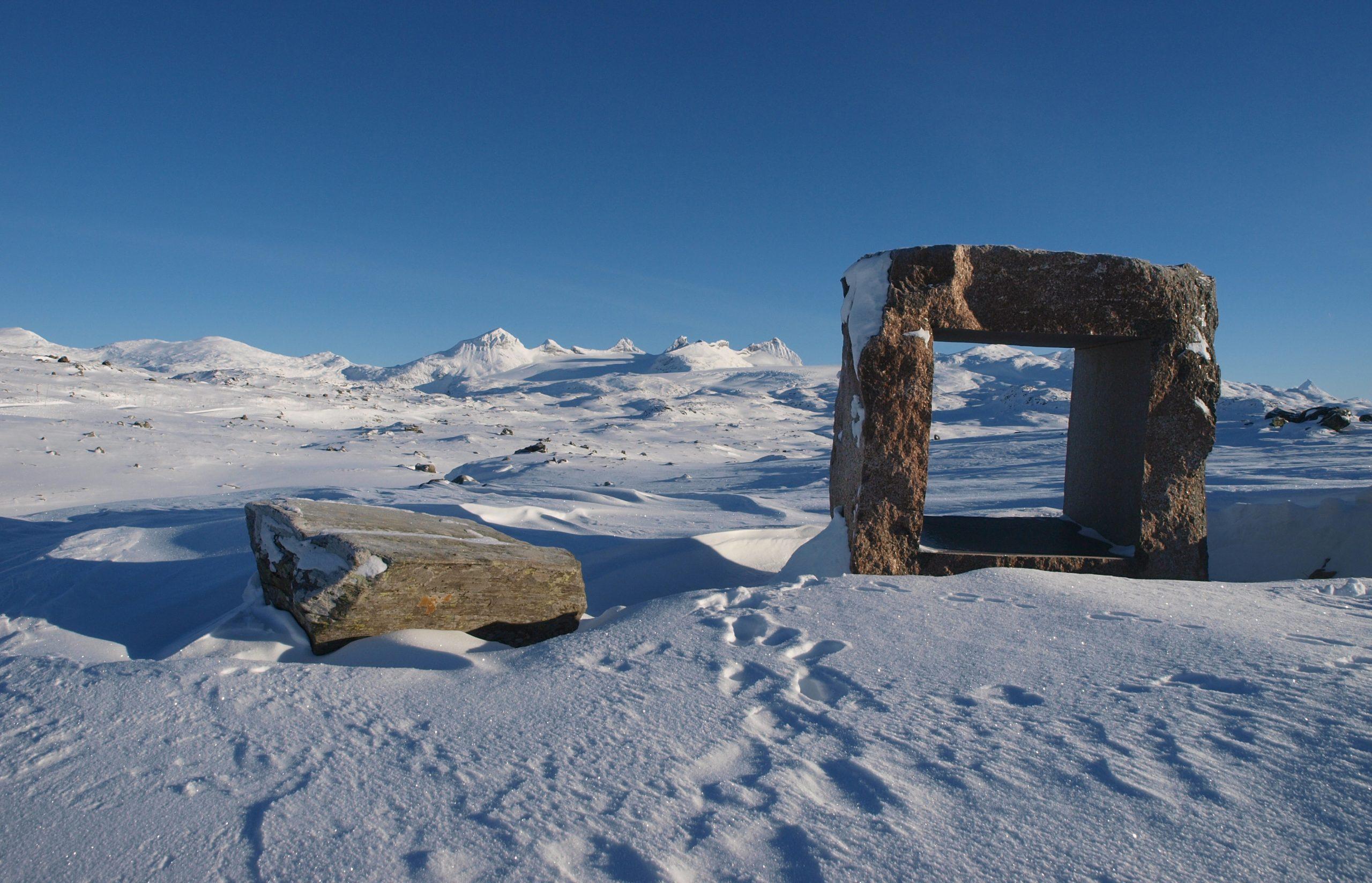 Landemerke ved Nasjonal turistveg Sognefjellet; steinskulptur laget av kunstneren Knut Wold. I bakgrunnen sees Smørstabbtindane, noen av Jotunheimens mer markante topper. Vegen over Sognefjellet er normalt stengt om vinteren, men enkelte år med lite snø kan den være åpen for trafikk langt utover senhøst og forvinter.