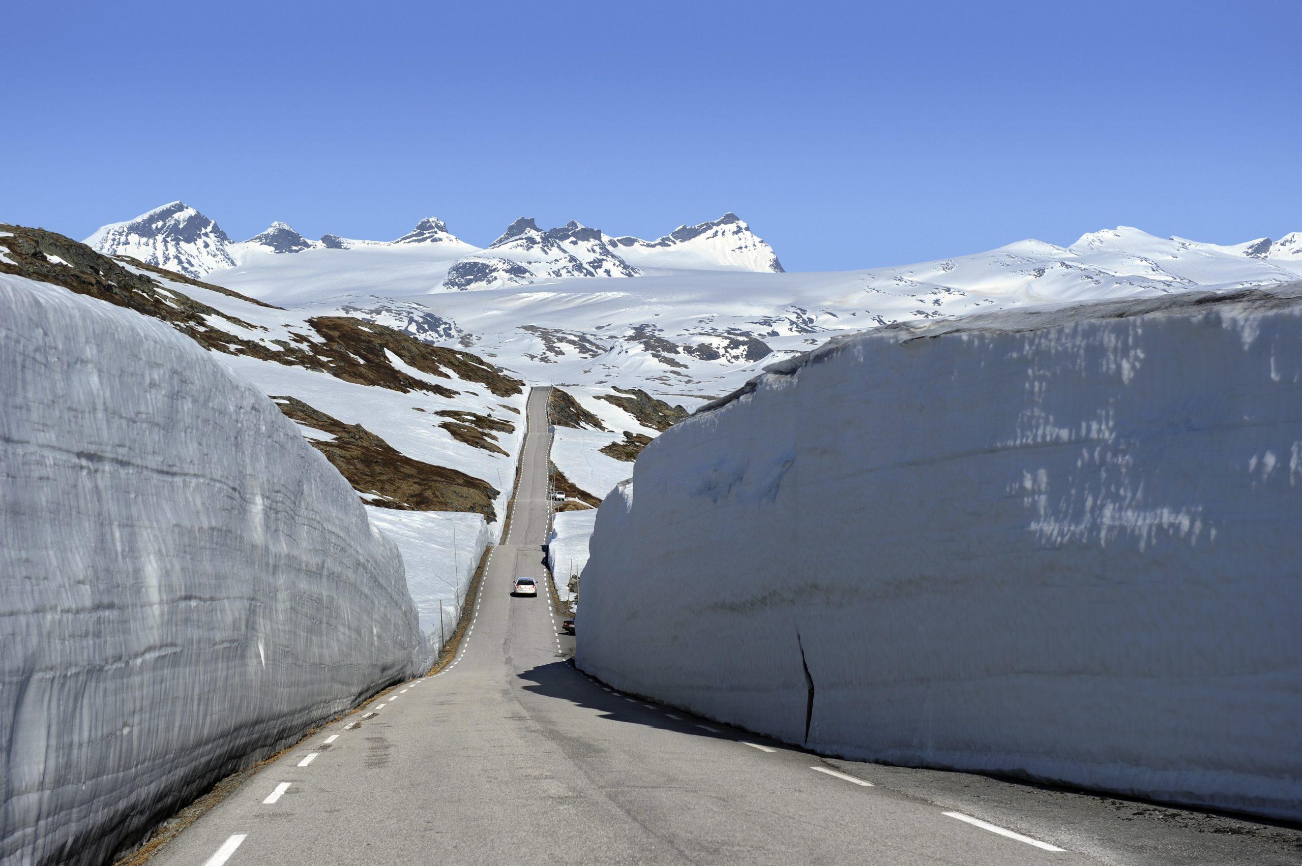 Riksveg 55 mellom brøytekanter ved Prestesteinsvatnet, Nasjonal Turistveg Sognefjellet. I det fjerne sees stortoppene ved Smørstabbreen.